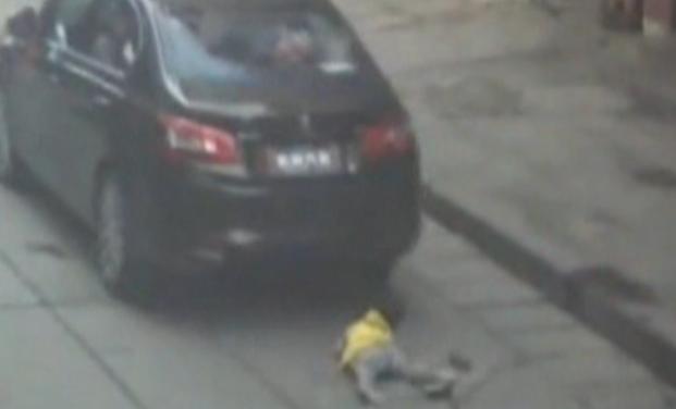 幼童过马路竟被圈入车底